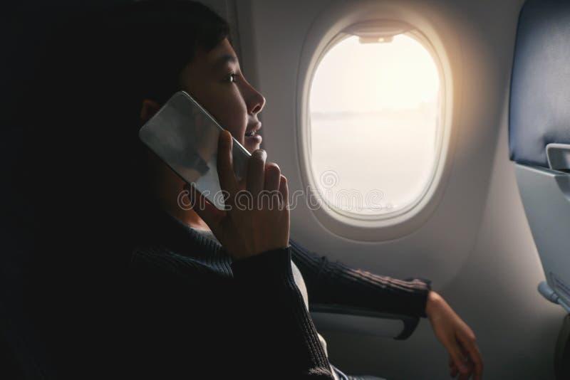 Donna asiatica turistica che si siede vicino alla finestra dell'aeroplano e che per mezzo dello Smart Phone durante il volo immagini stock