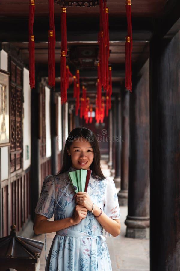 Donna asiatica in un tempio che tiene un ventaglio immagini stock libere da diritti