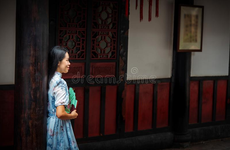Donna asiatica in un tempio che tiene un ventaglio fotografia stock