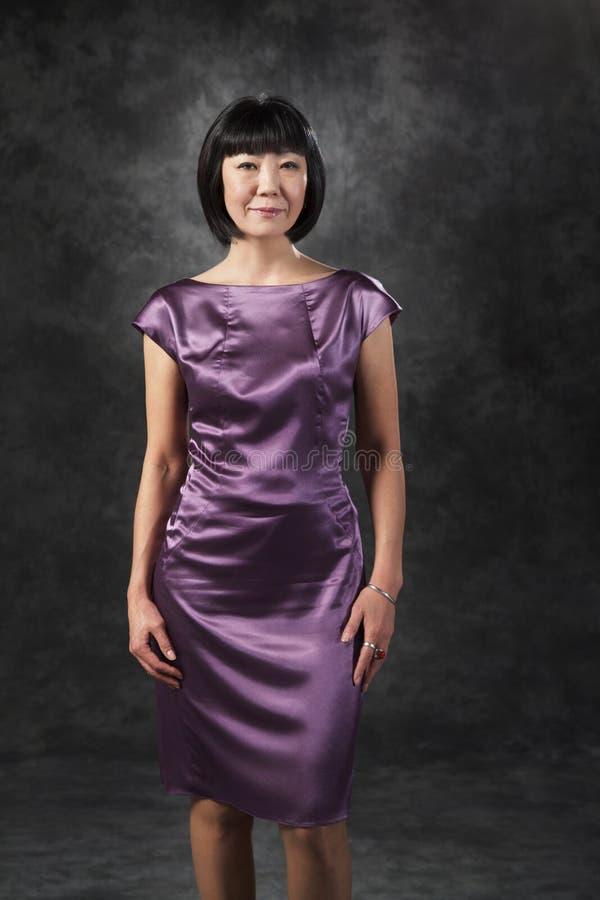 Donna asiatica in vestito porpora fotografie stock