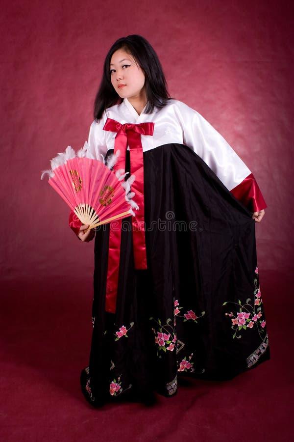 Donna asiatica in vestito tradizionale con il ventilatore fotografie stock