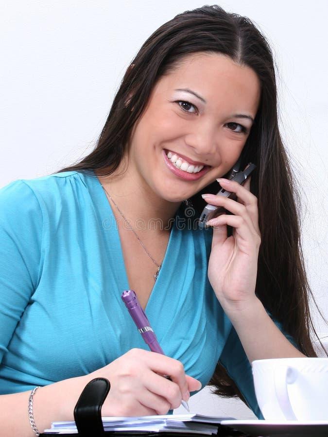 Donna Asiatico-Americana con il cellulare ed il Datebook fotografie stock