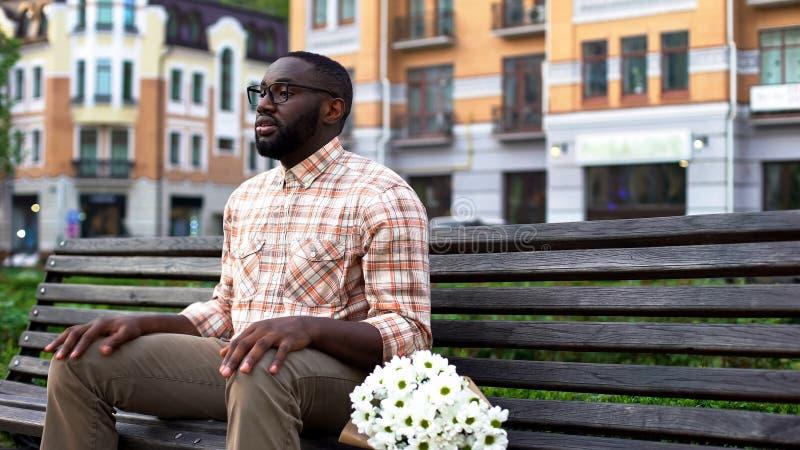 Donna aspettante del giovane maschio, sedentesi sul banco di parco con i fiori, appuntamento al buio immagine stock
