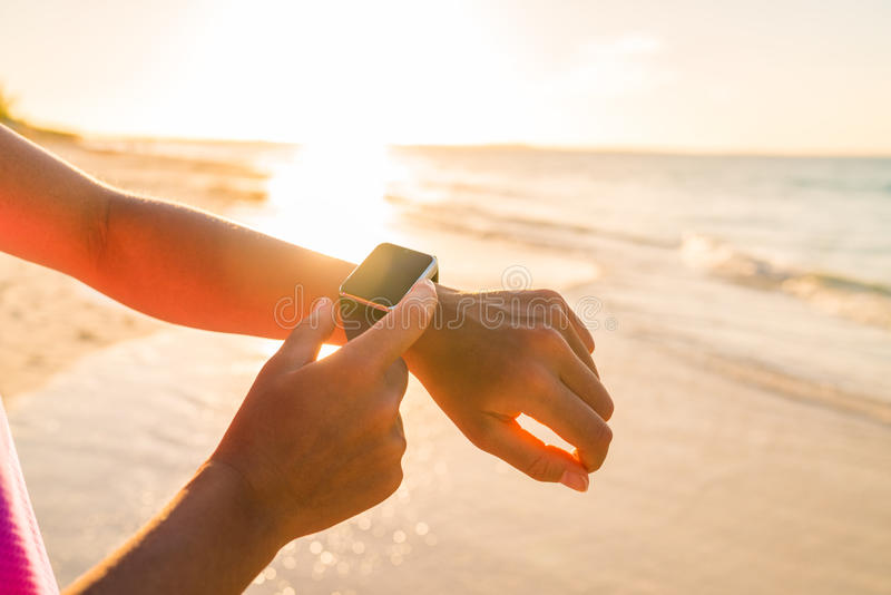 Donna astuta dell'orologio che usando smartwatch su attività fotografie stock