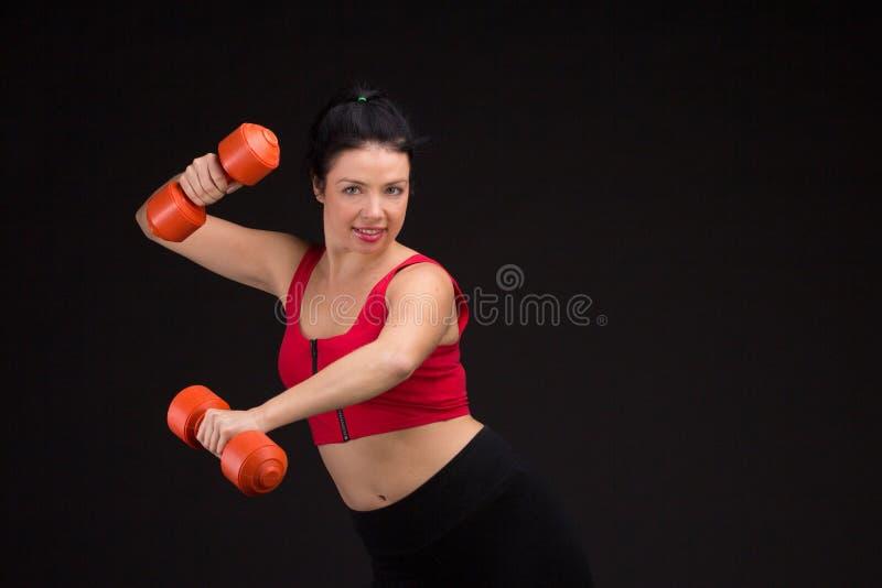 Donna atletica brutale che pompa sui muscules con le teste di legno fotografia stock libera da diritti
