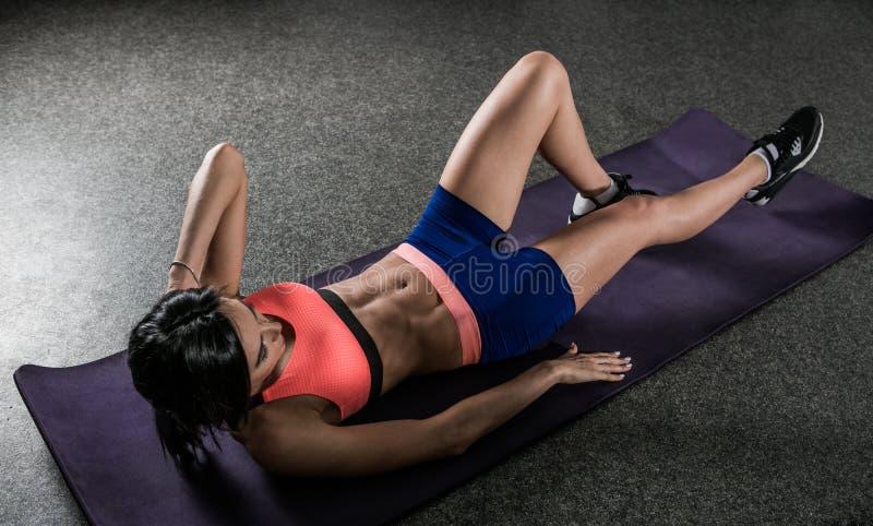 Donna atletica che lavora gli intervalli di ab nella forma fisica immagine stock