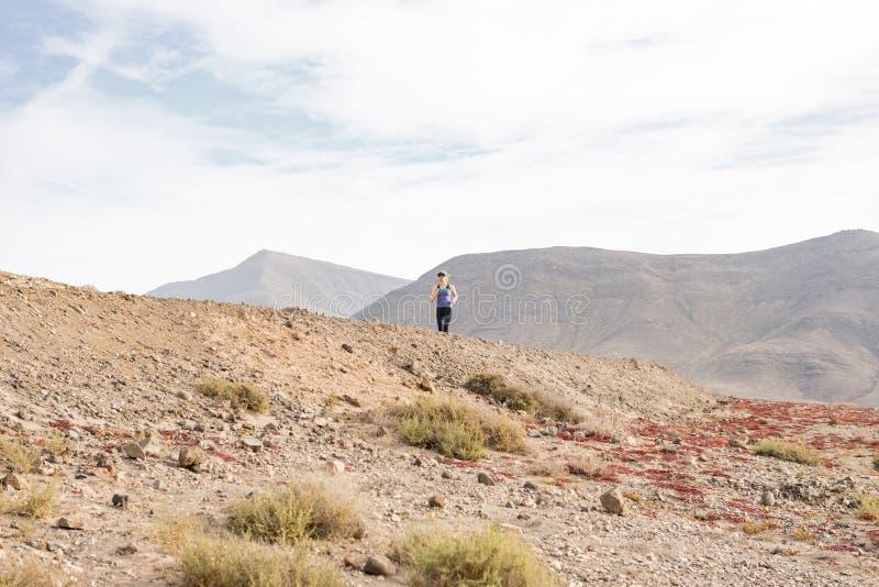 Donna atletica che pareggia sulla traccia del deserto da una distanza fotografia stock libera da diritti