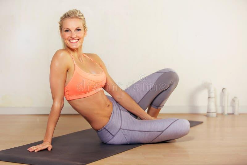 Donna atletica che si distende dopo l'allenamento di yoga immagini stock libere da diritti