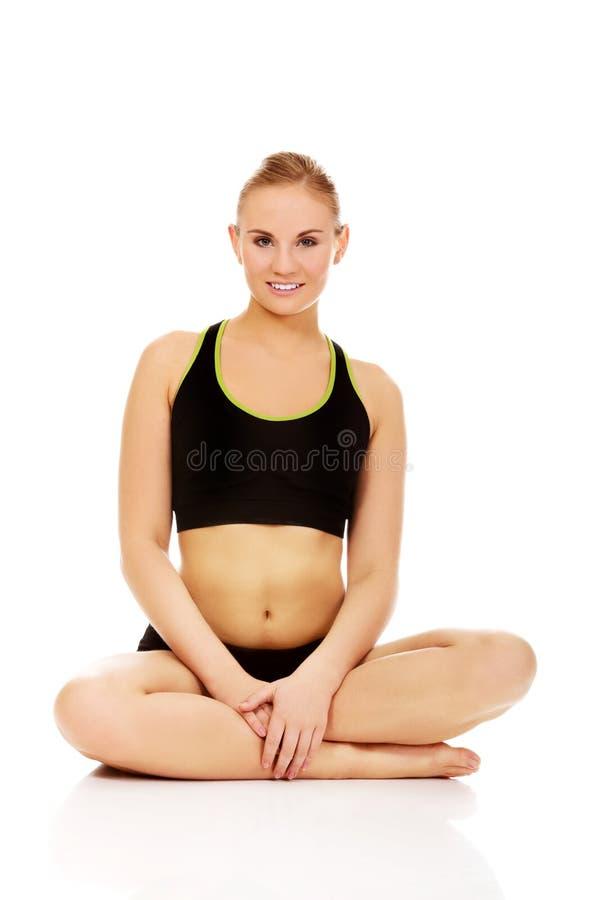 Donna atletica che si siede fornito di gambe trasversale sul pavimento fotografia stock libera da diritti