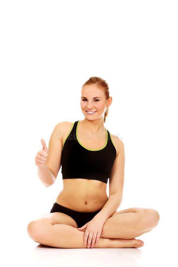 Donna atletica che si siede fornito di gambe trasversale sul pavimento e sul pollice di manifestazione su fotografie stock