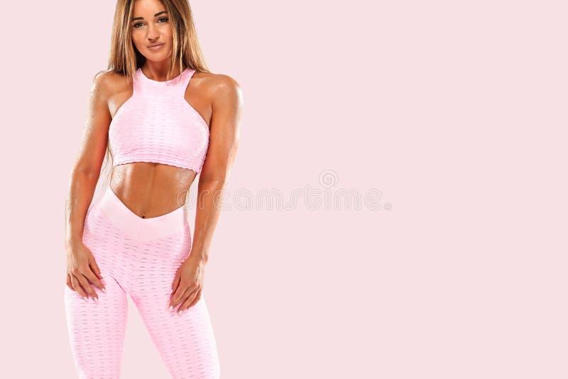 Donna atletica dei giovani fitenss nei bei abiti sportivi rosa, contro un fondo bianco fotografia stock libera da diritti