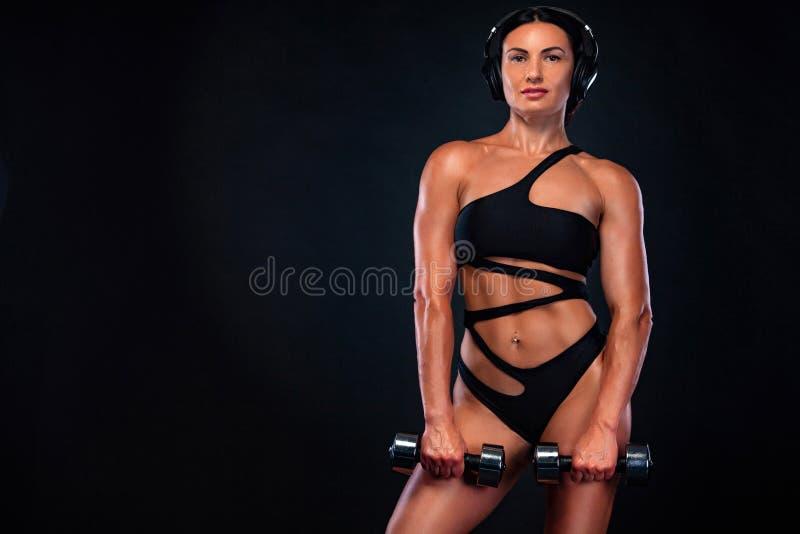 Donna atletica del forte culturista muscolare che pompa sui muscoli con le teste di legno su fondo nero Culturismo di allenamento immagini stock