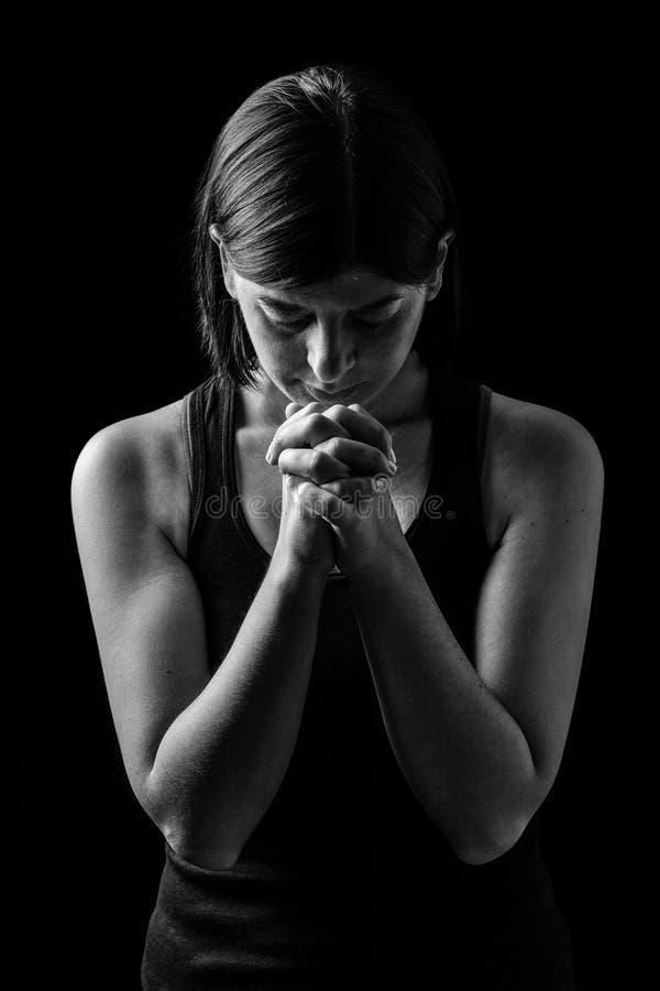 Donna atletica fedele che prega, con le mani piegate nel culto al dio fotografia stock