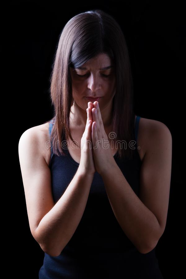 Donna atletica fedele che prega, con le mani piegate nel culto al dio fotografie stock libere da diritti