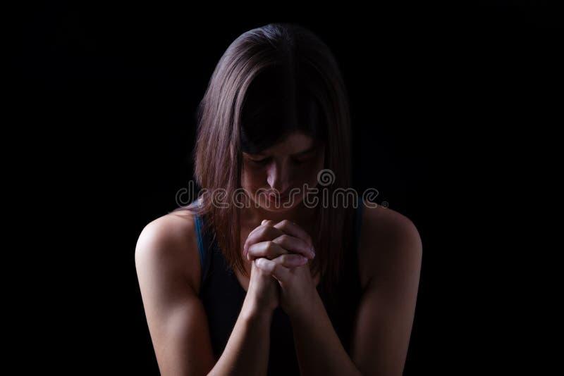 Donna atletica fedele che prega, con le mani piegate nel culto al dio immagine stock libera da diritti