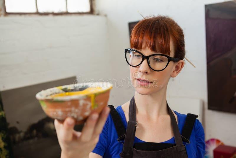 Donna attenta che esamina ciotola dipinta immagini stock libere da diritti