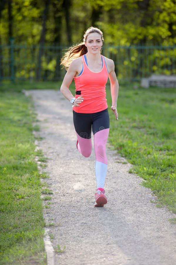 Donna attiva in buona salute di forma fisica di estate che corre sul parco fotografie stock
