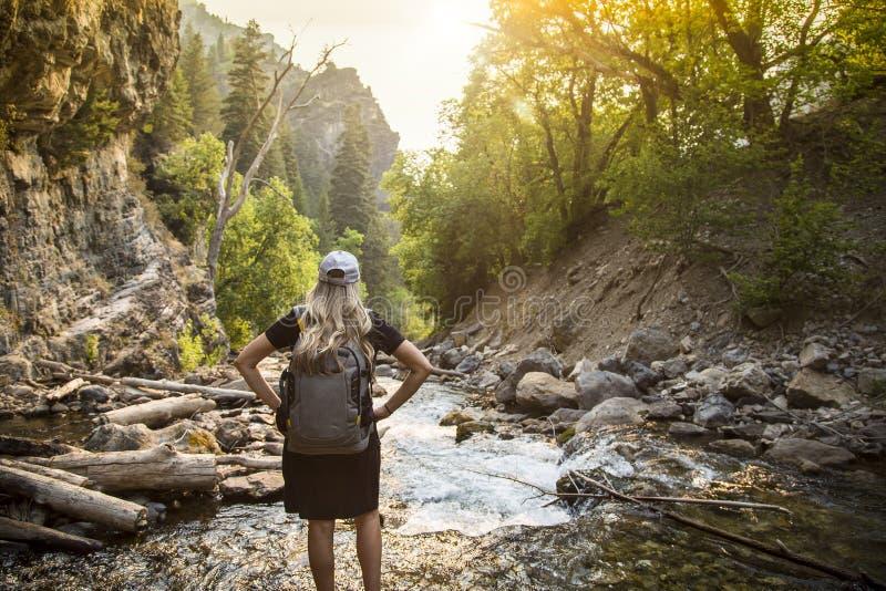 Donna attiva che fa un'escursione attraverso una torrente montano su un aumento immagini stock