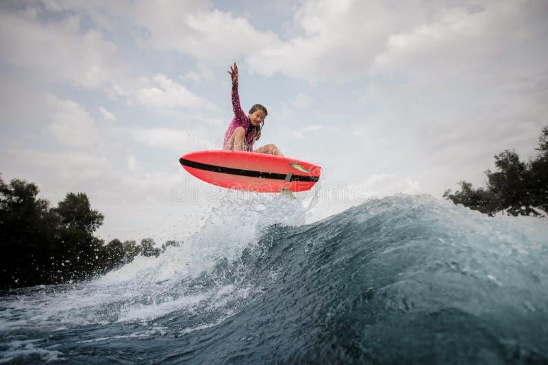 Donna attiva che salta sull'onda di taglio blu contro il grey immagine stock libera da diritti