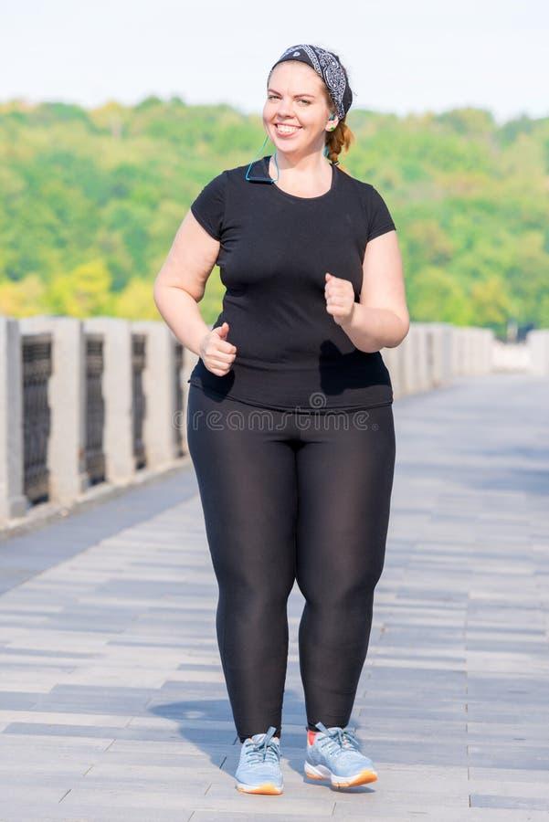 donna attiva grassa che lavora alla sua figura - funzionamento di mattina immagine stock