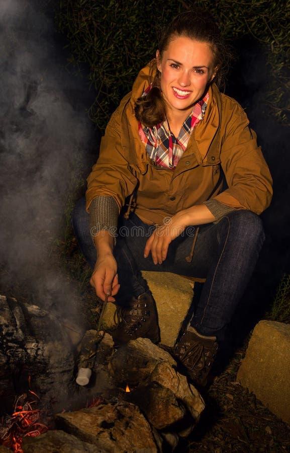 Donna attiva sorridente del viaggiatore dalla caramella gommosa e molle di torrefazione del falò fotografia stock