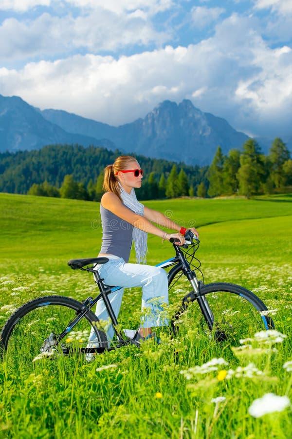 Donna attiva sulla bicicletta in montagne immagine stock libera da diritti