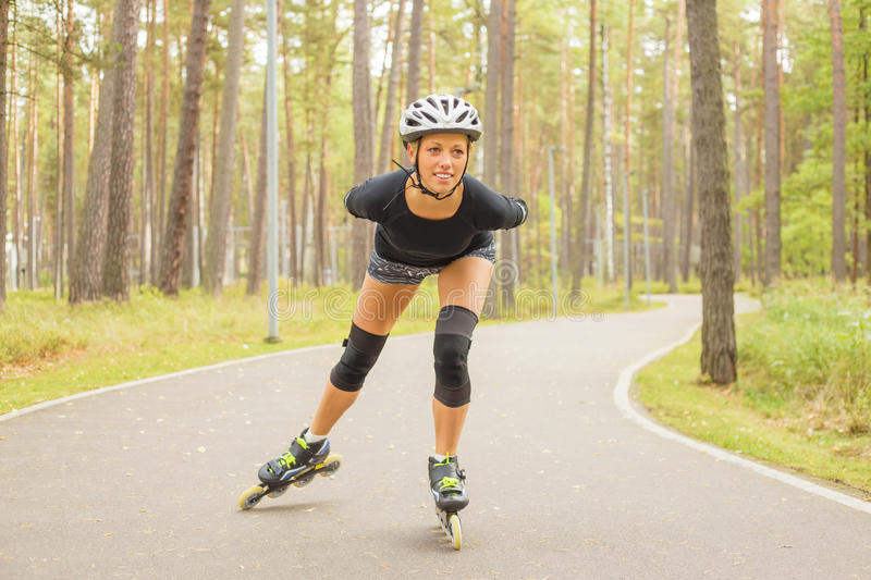 Donna attiva sulla formazione dei pattini di rullo fotografia stock
