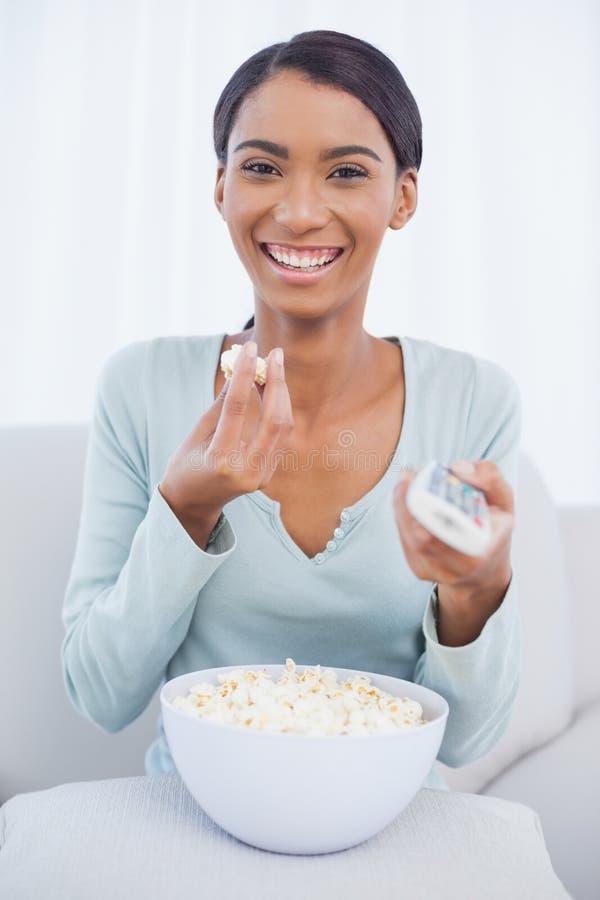 Donna attraente allegra che mangia popcorn mentre guardando TV immagini stock