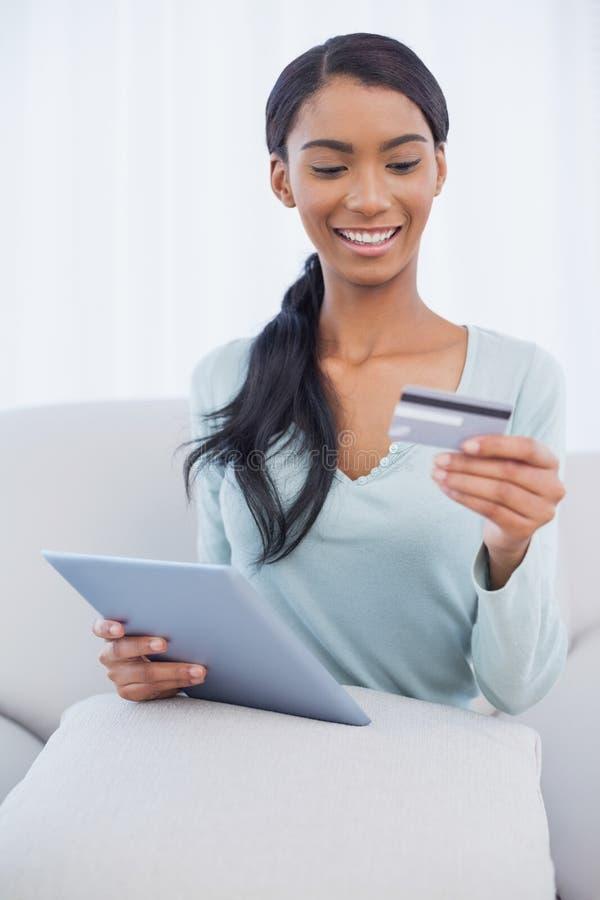 Donna attraente allegra che per mezzo del suo pc della compressa per comprare online immagine stock libera da diritti