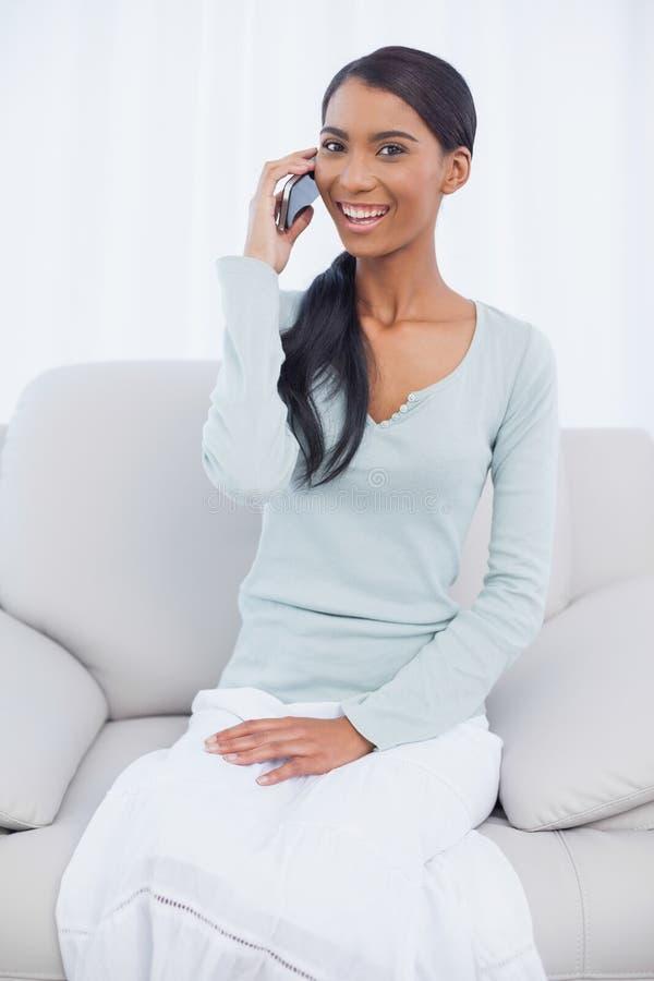 Donna attraente allegra che si siede sul sofà accogliente che ha una telefonata immagini stock libere da diritti