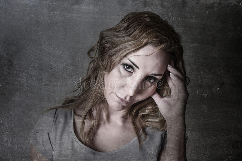 Donna attraente bionda sui suoi anni trenta tristi e depressi esaminando la macchina fotografica nel dispiacere e nel dolore immagine stock libera da diritti