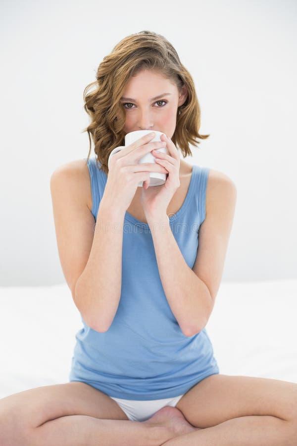 Donna attraente calma che si siede sul suo letto che beve dalla tazza bianca fotografie stock