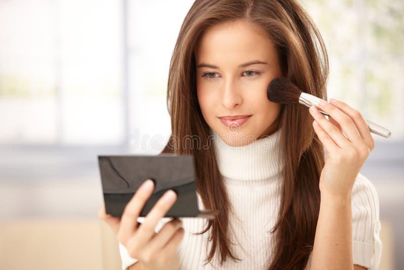 Donna attraente che applica trucco fotografie stock libere da diritti