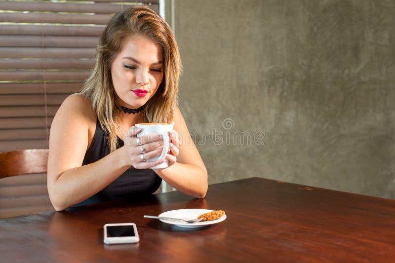 Donna attraente che beve una bevanda calda fotografia stock libera da diritti