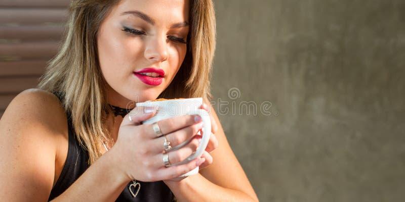 Donna attraente che beve una bevanda calda immagine stock