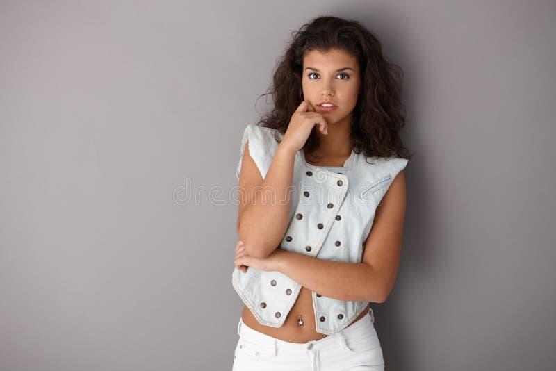 Donna attraente che controlla fondo grigio immagine stock