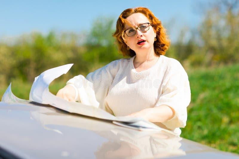 Donna attraente che controlla posizione in mappa di carta sul cofano fotografia stock