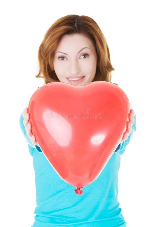 Donna attraente che dà un cuore del baloon. fotografia stock