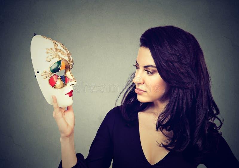 Donna attraente che esamina la maschera tradizionale di carnevale fotografie stock