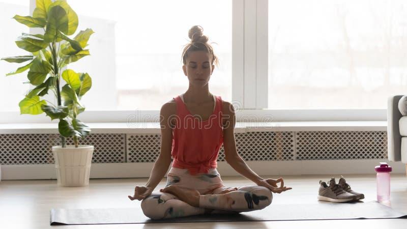 Donna attraente che fa esercizio di yoga che medita posizione di loto di seduta fotografia stock