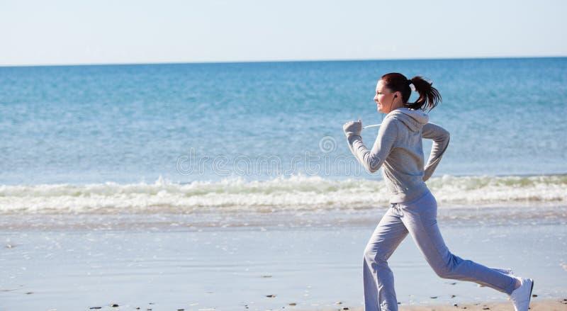 Donna attraente che funziona sulla spiaggia fotografia stock
