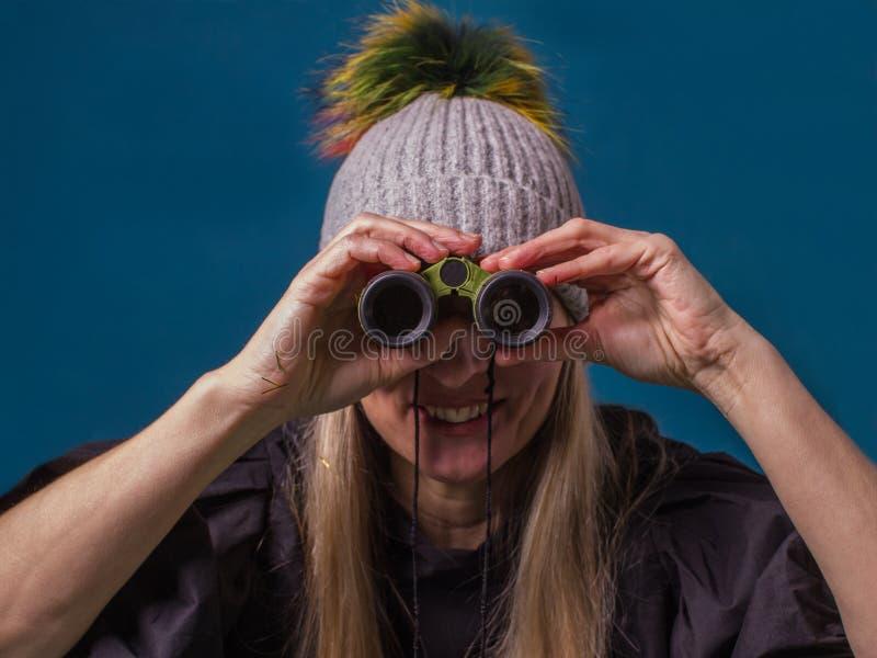 Donna attraente che guarda con un binoculare Obiettivo, futuro e fotografia stock