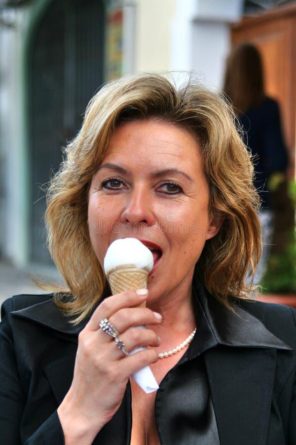 Donna attraente che mangia il gelato davanti ad un salone di gelato italiano, Gelateria fotografie stock libere da diritti