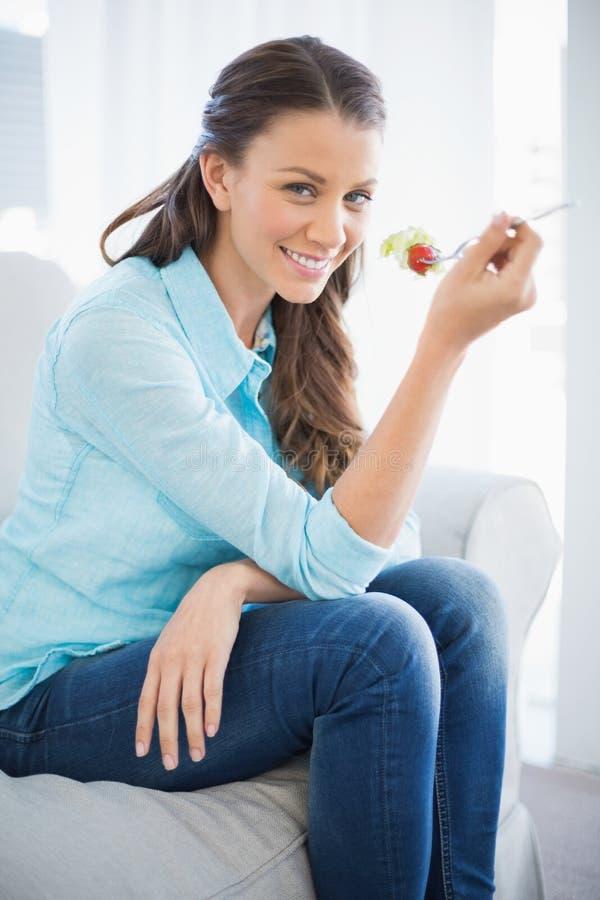 Donna attraente che mangia insalata sana immagine stock