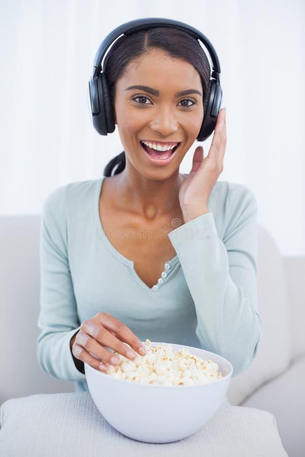 Donna attraente che mangia popcorn mentre ascoltando la musica fotografia stock