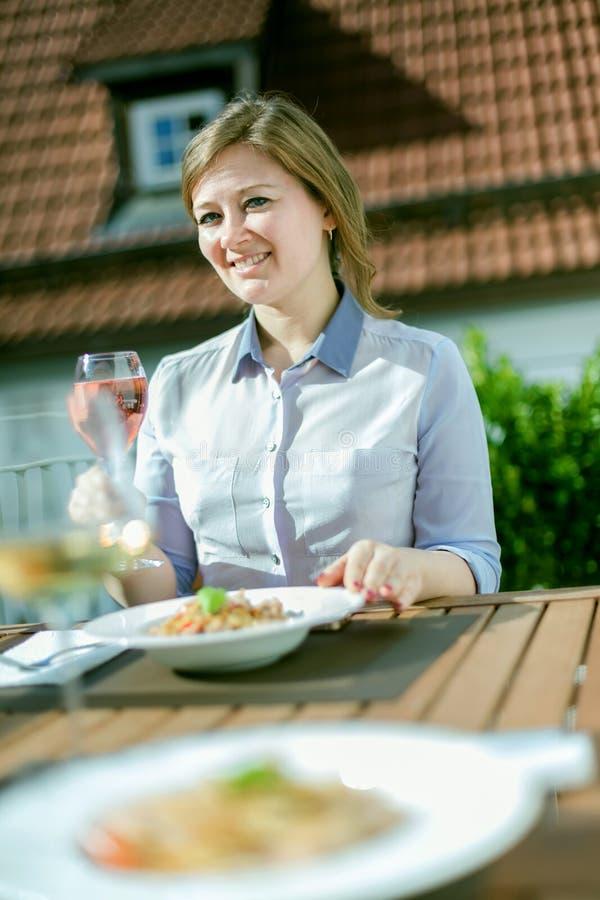 Donna attraente che mangia prima colazione sul suo balcone domestico fotografia stock libera da diritti