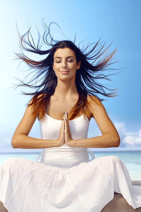 Donna attraente che medita su spiaggia fotografia stock