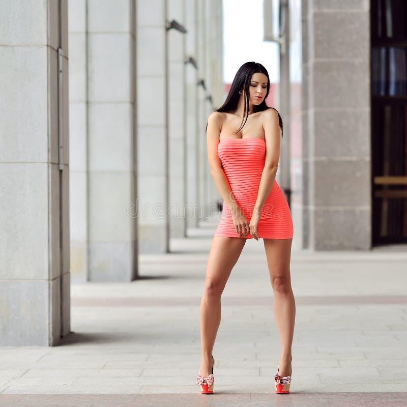Donna attraente che porta vestito rosso e che posa nella città immagini stock libere da diritti