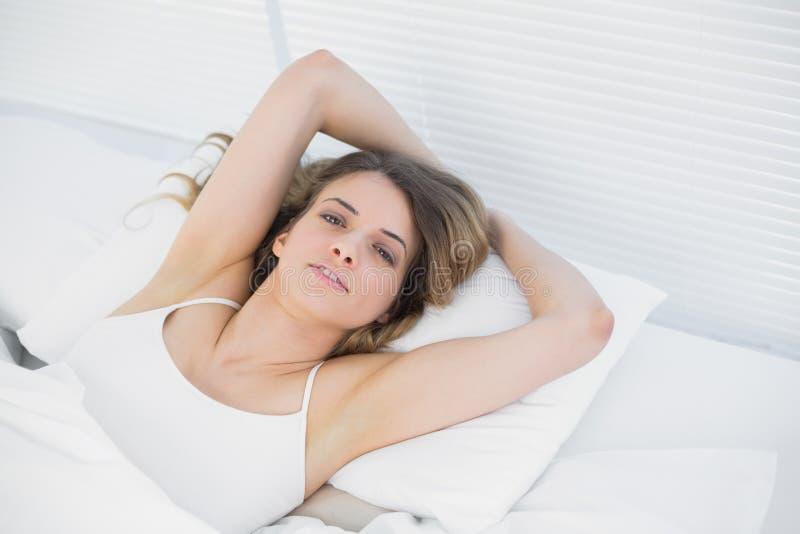 Donna attraente che posa menzogne sul suo letto immagine stock