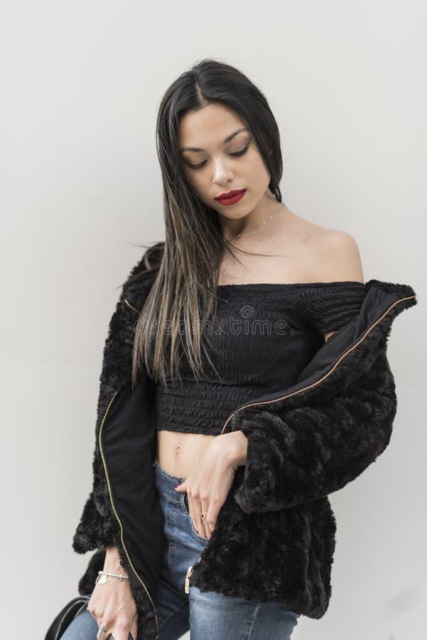 Donna attraente che posa nel fondo all'aperto bianco fotografie stock libere da diritti